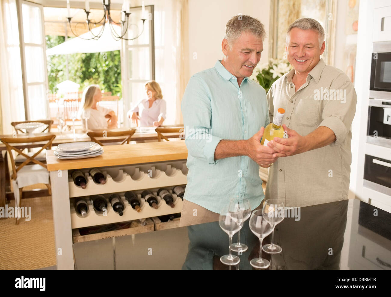 Senior me looking at wine bottle in kitchen Stock Photo