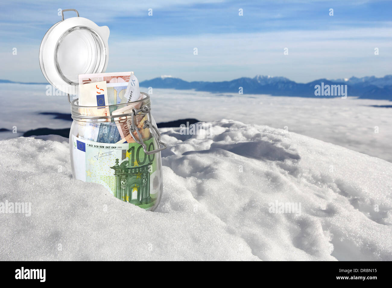 Euro banknotes in jar in the snow on the mountain top - Stock Image