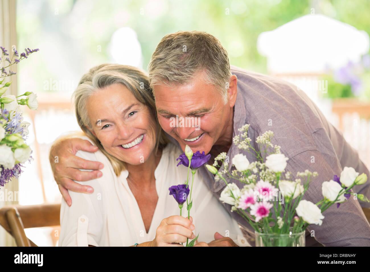 Senior couple smelling flowers - Stock Image