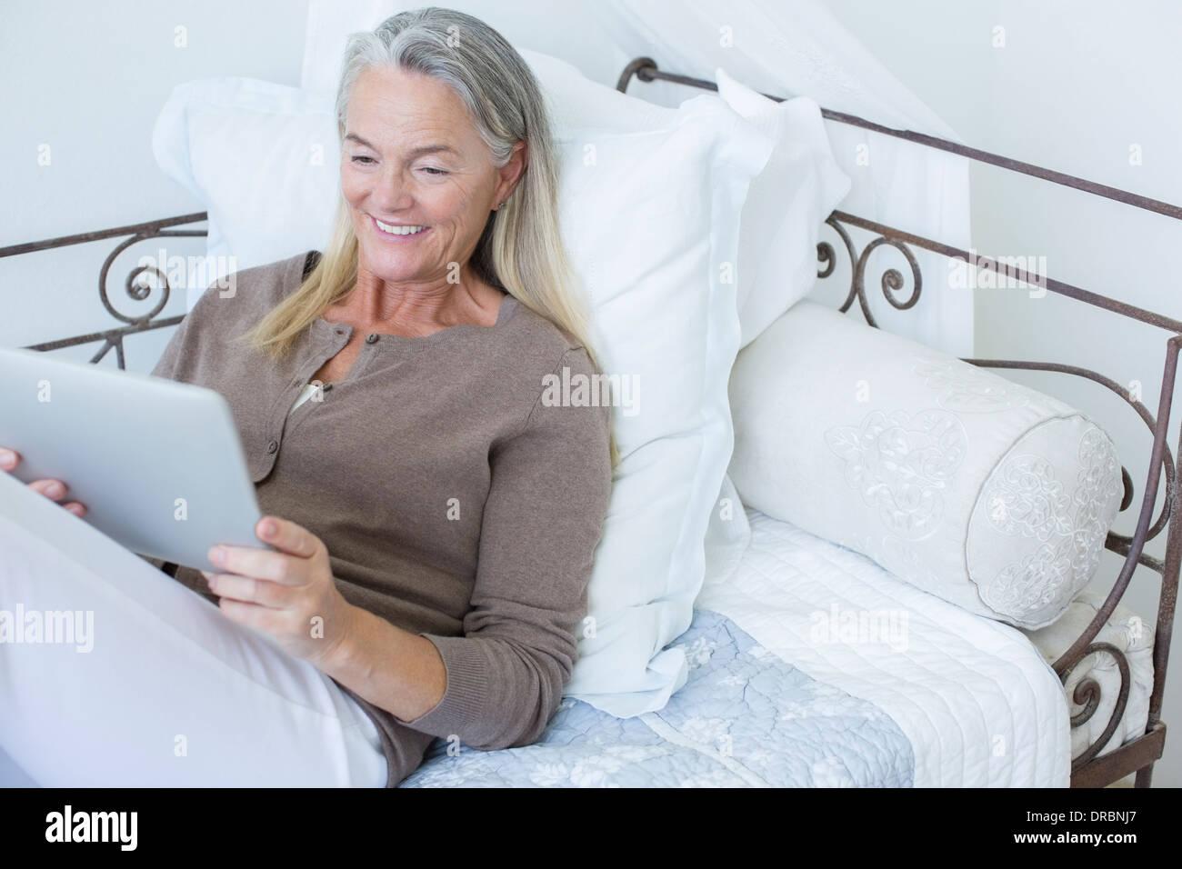 Senior woman using digital tablet on bed - Stock Image