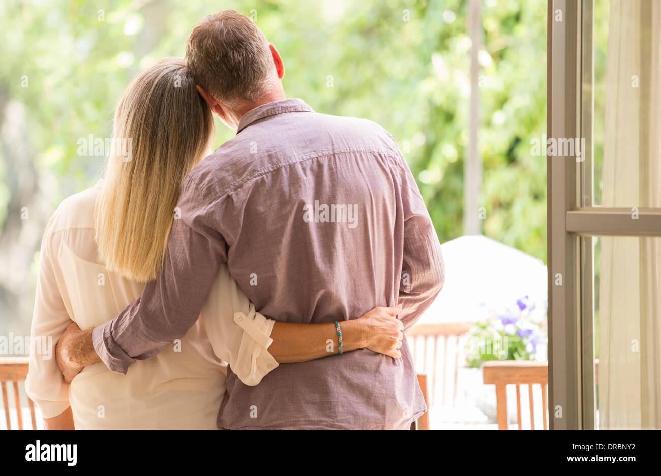 Senior couple hugging in doorway - Stock Image