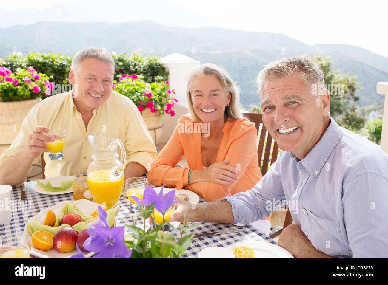 Senior friends enjoying breakfast on balcony - Stock Image