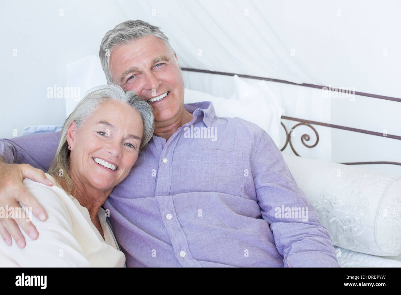 Senior couple laying on bed - Stock Image