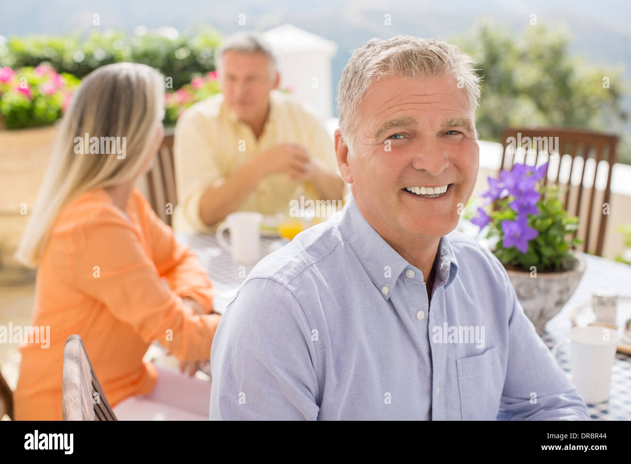 Senior man smiling at patio table - Stock Image