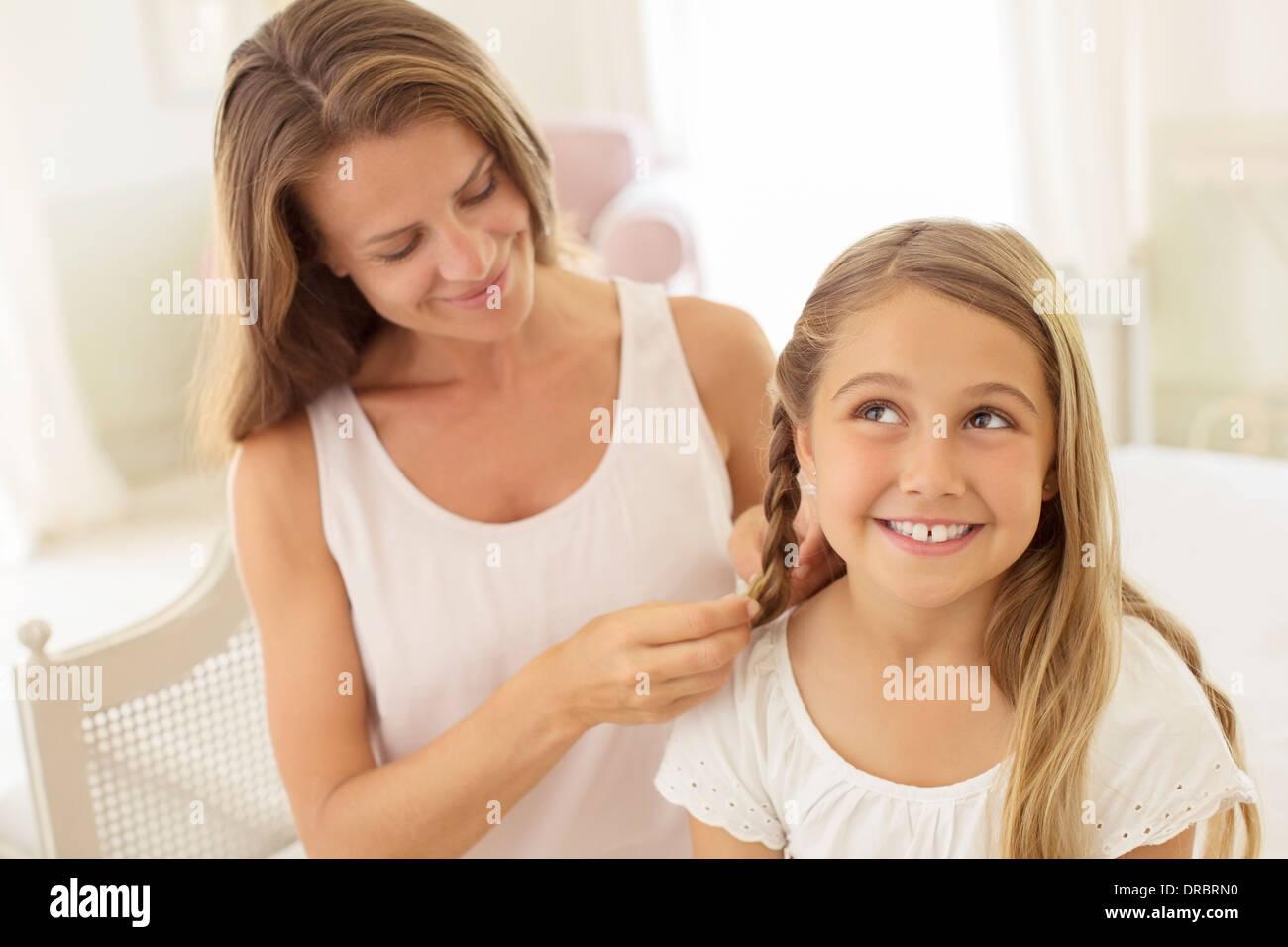 Mother braiding daughter's hair - Stock Image