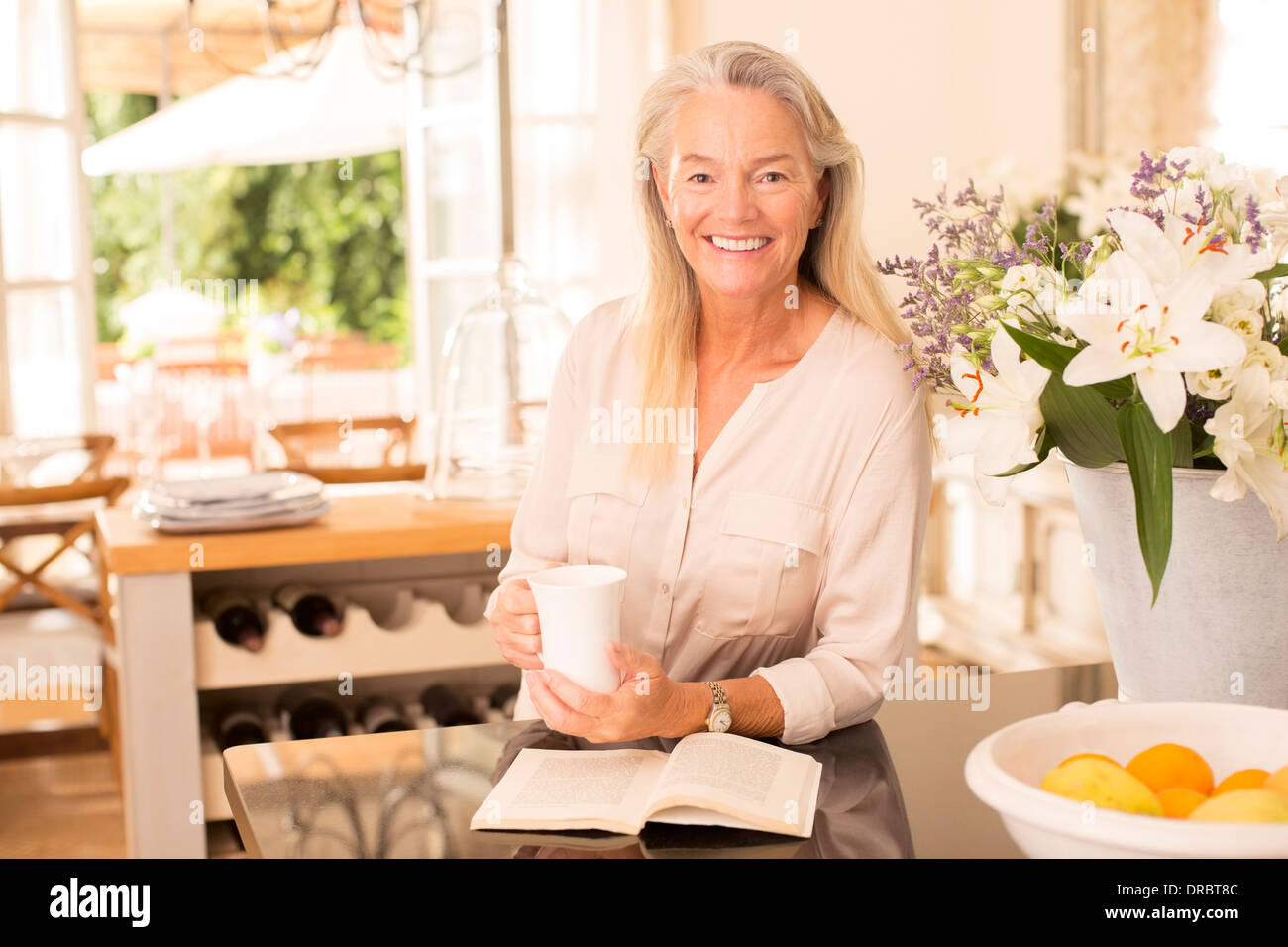 Senior woman drinking coffee and reading book in kitchen Stock Photo