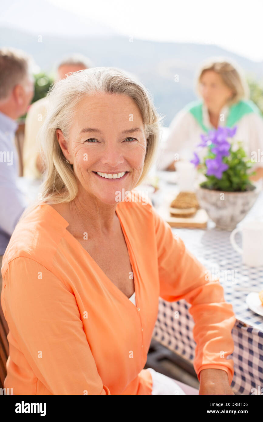 Senior woman smiling at patio table - Stock Image