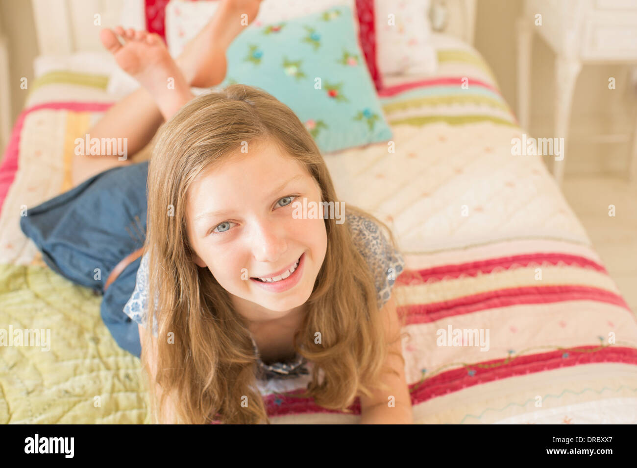 Smiling girl laying on bed - Stock Image
