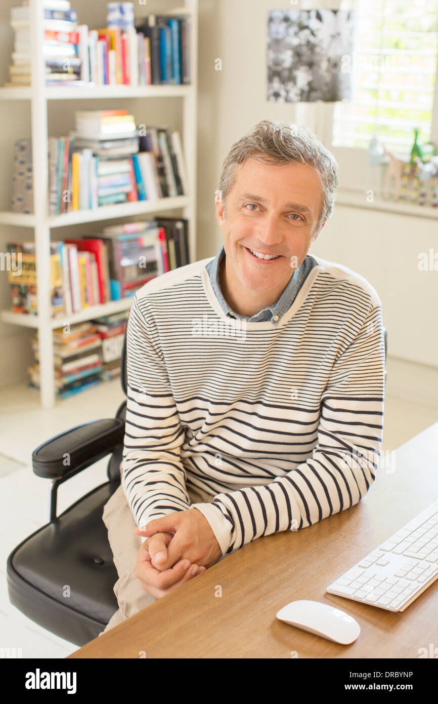 Man smiling at computer desk - Stock Image
