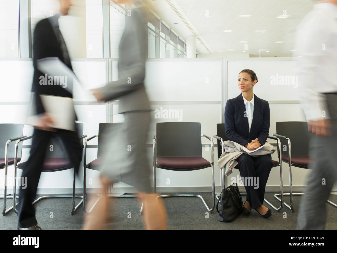 Businesswoman sitting in busy waiting area - Stock Image