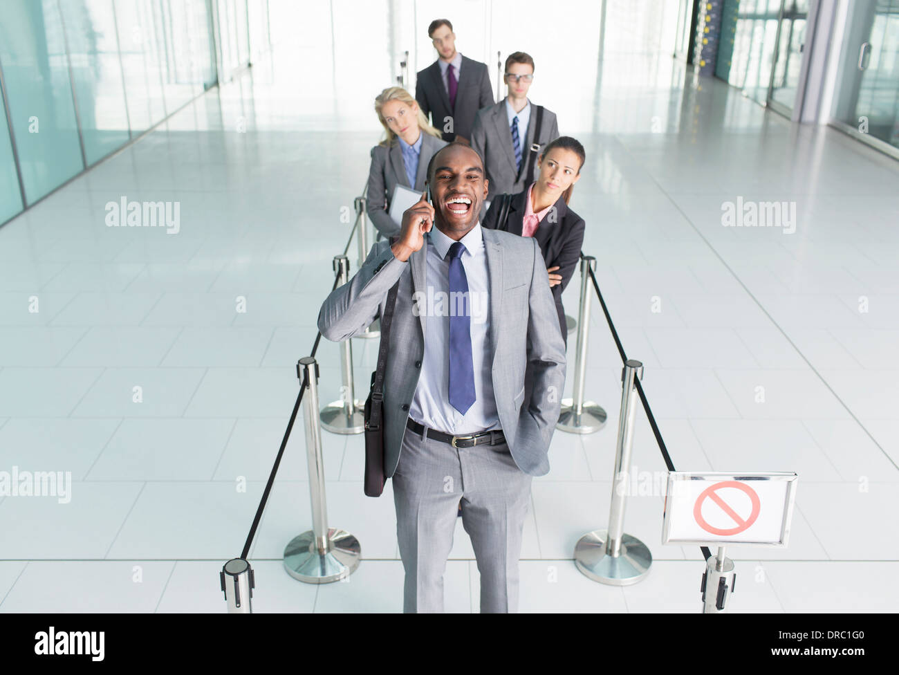 Businessman talking on cell phone in line - Stock Image