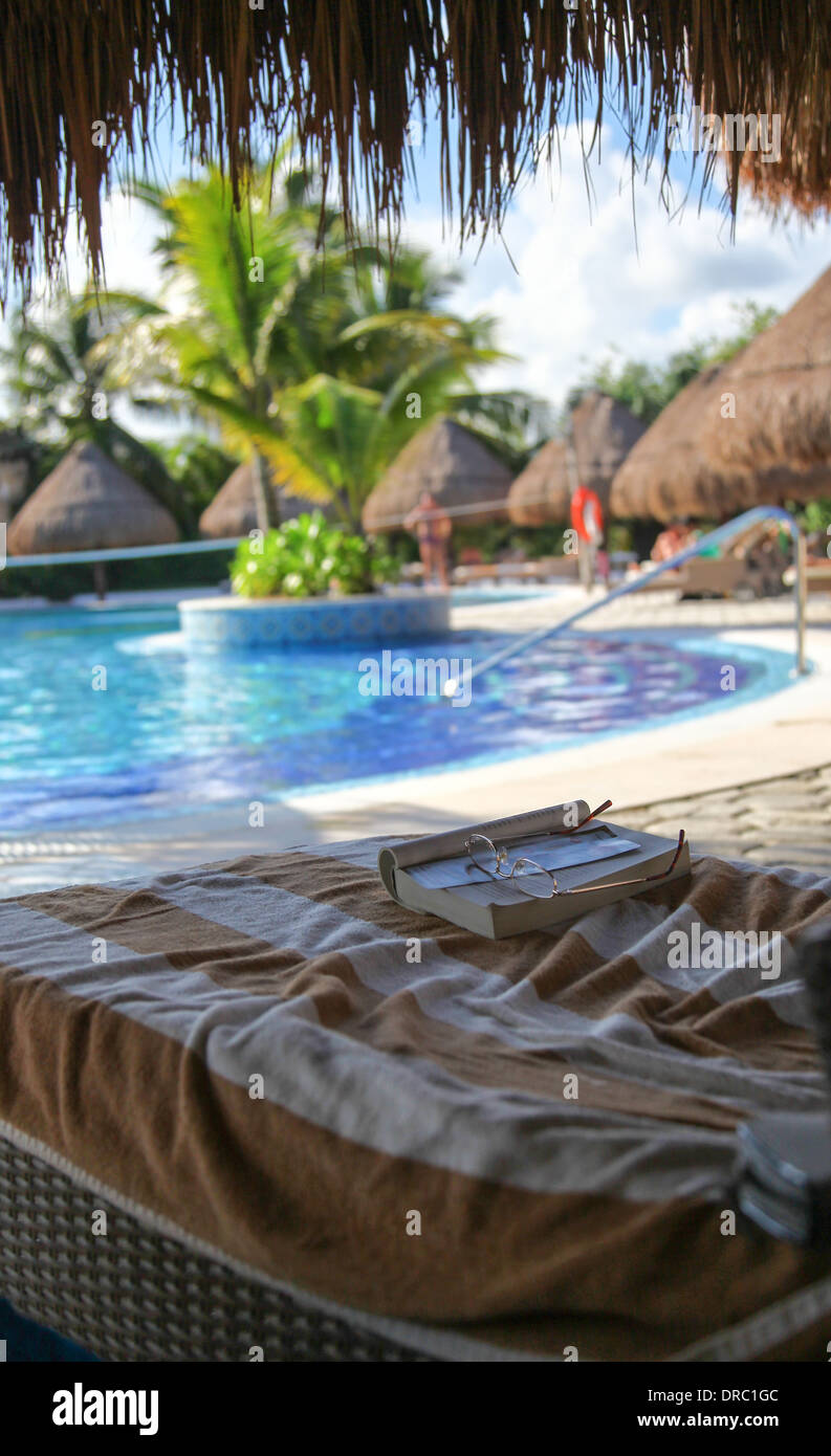 A paperback book and reading glasses on a reclining chair next to the swimming pool luxury 5 star hotel Catalonia Royal Tulum - Stock Image