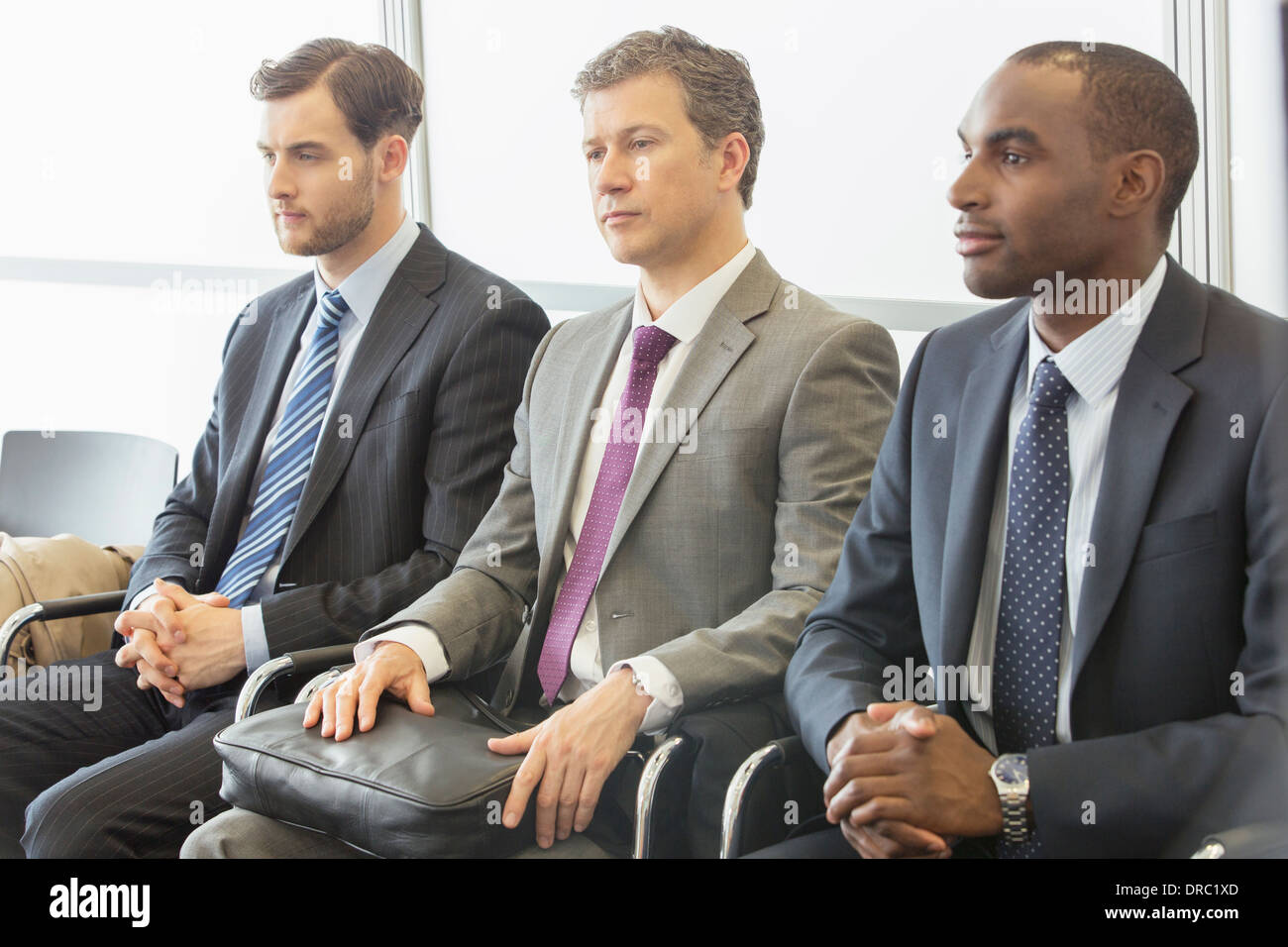 Businessmen sitting in waiting area - Stock Image