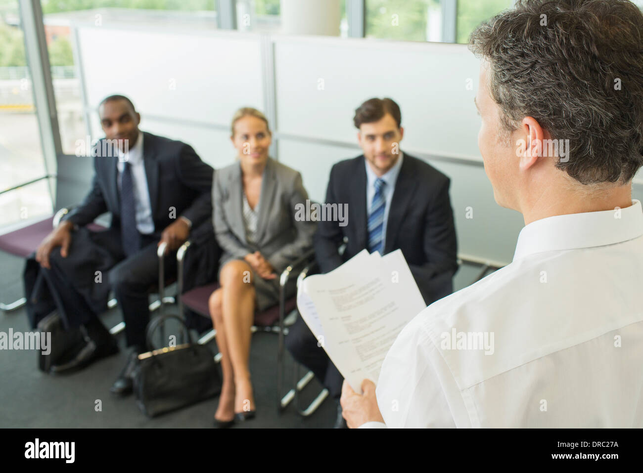 Businessman talking to colleagues in office - Stock Image
