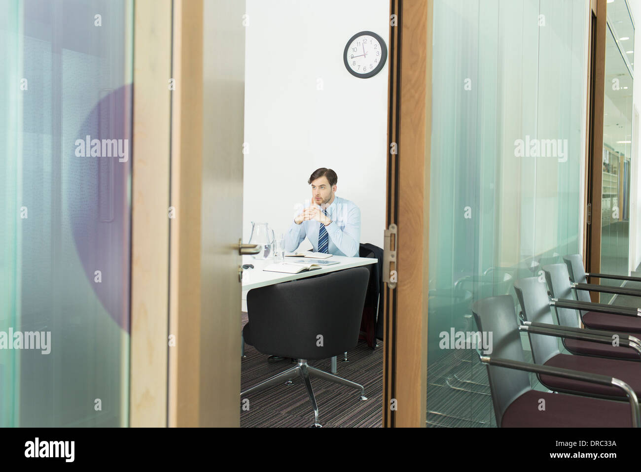 Businessman sitting in office - Stock Image
