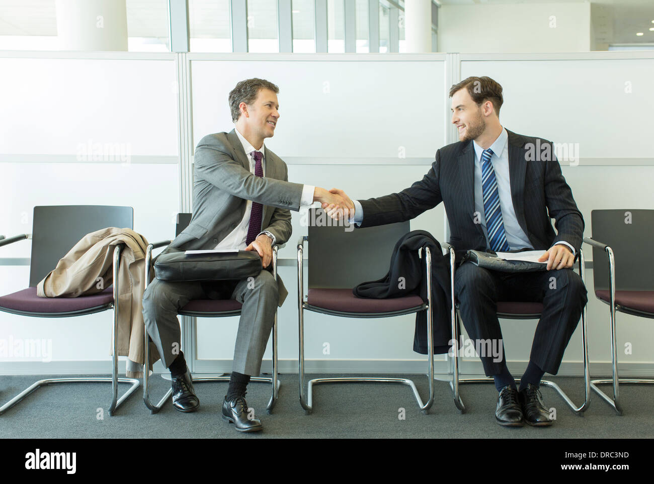 Businessmen shaking hands in waiting area - Stock Image