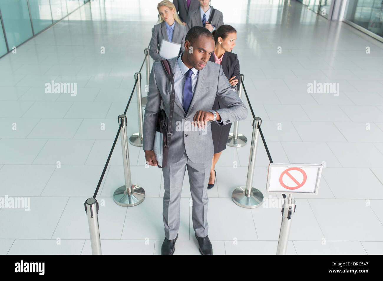 Businessman waiting in line - Stock Image