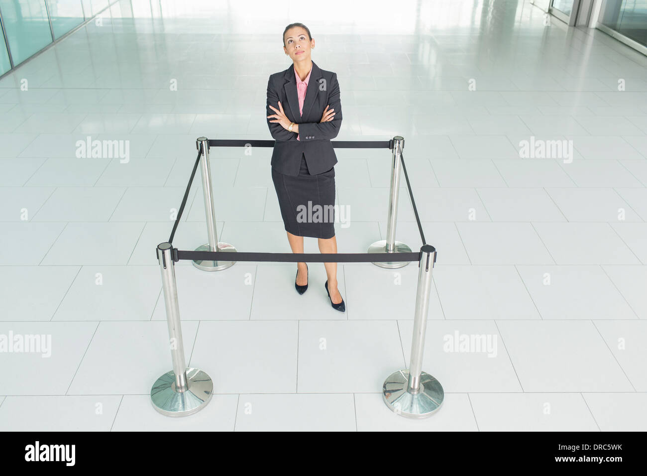 Businesswoman standing in roped-off square - Stock Image