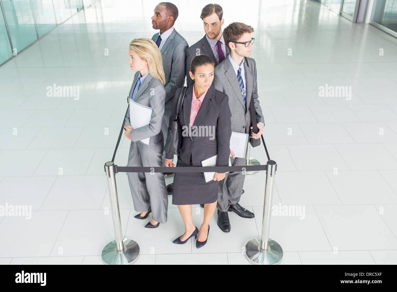Business people standing in roped-off square - Stock Image