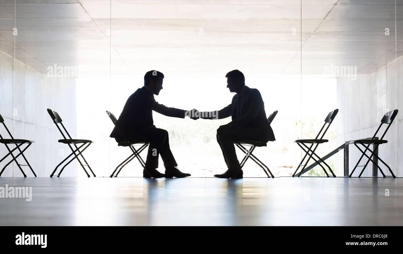 Businessmen shaking hands in office - Stock Image