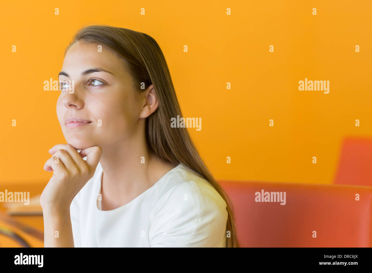 Pensive businesswoman with hand on chin - Stock Image