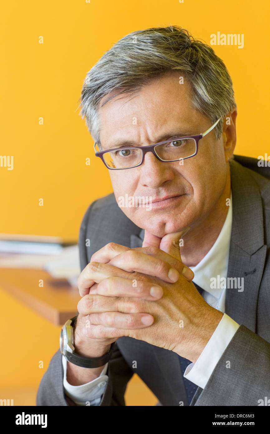 Businessman with hands clasped - Stock Image