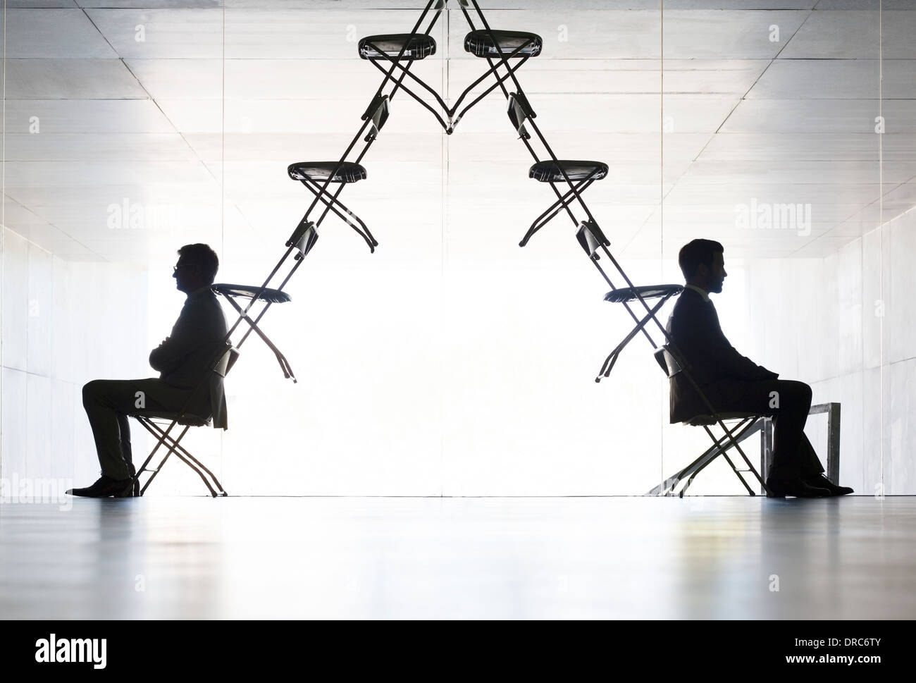 Businessmen sitting at opposite ends of office chair installation art - Stock Image