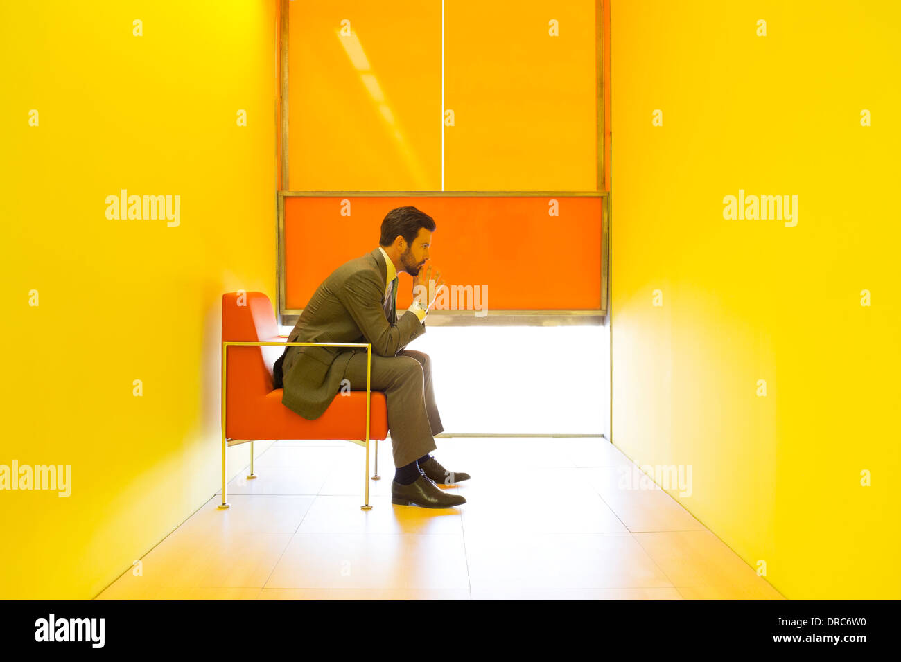 Businessman thinking in bright office - Stock Image
