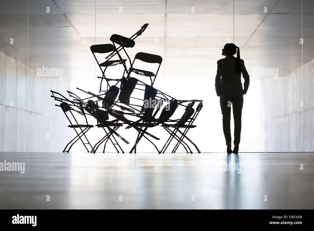 Businesswoman examining office chair installation art - Stock Image