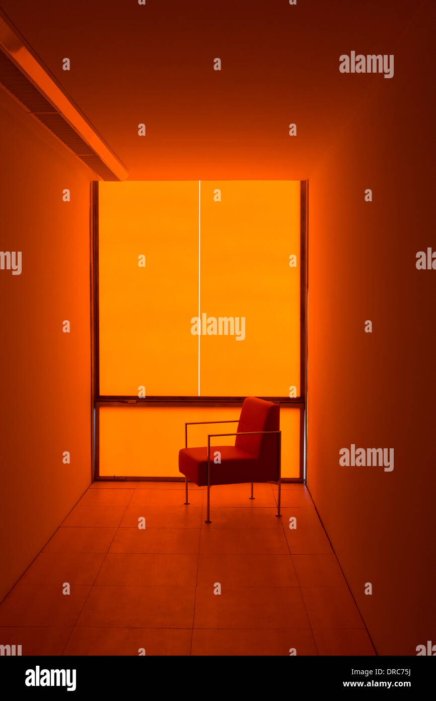 Chair at window in orange office - Stock Image