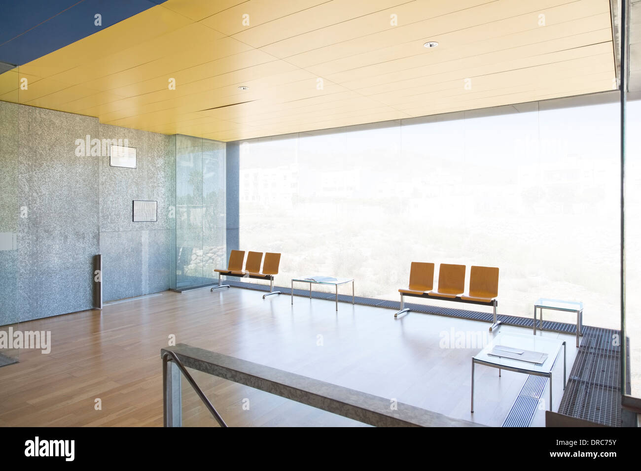 Chairs at window in empty lobby - Stock Image