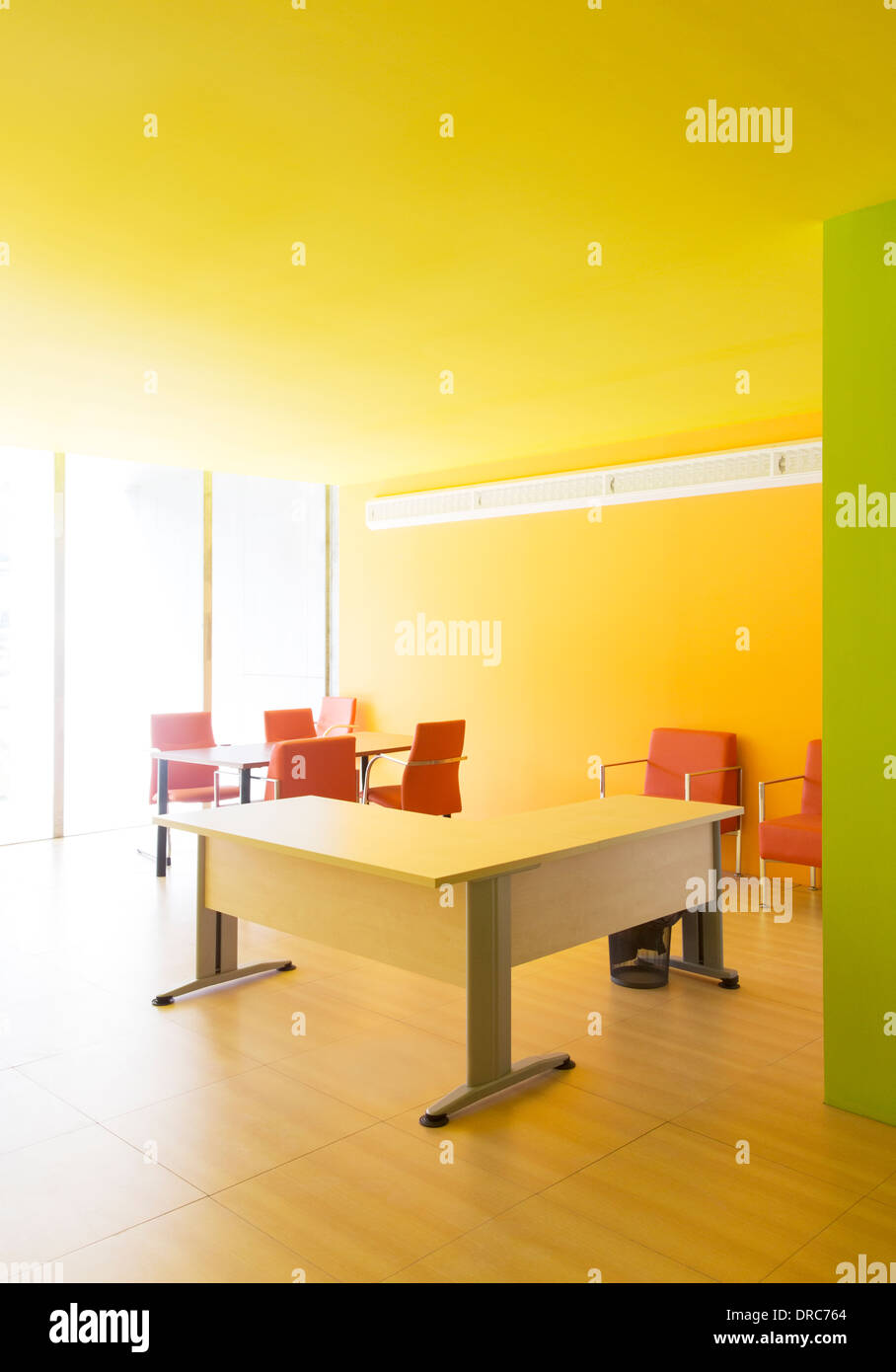 Desks and chairs in bright office - Stock Image