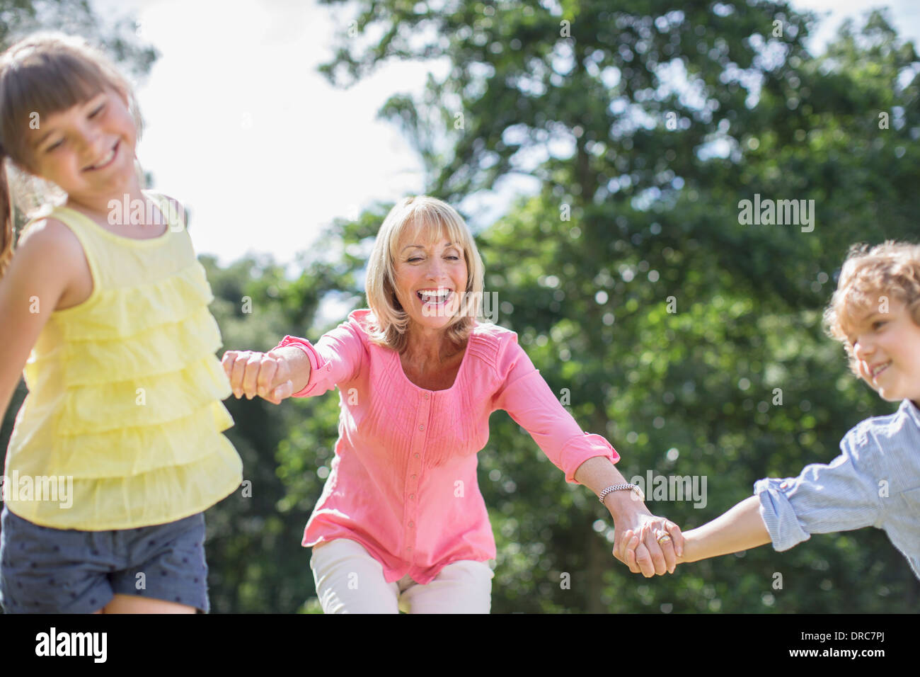 Grandmother and grandchildren playing outdoors - Stock Image