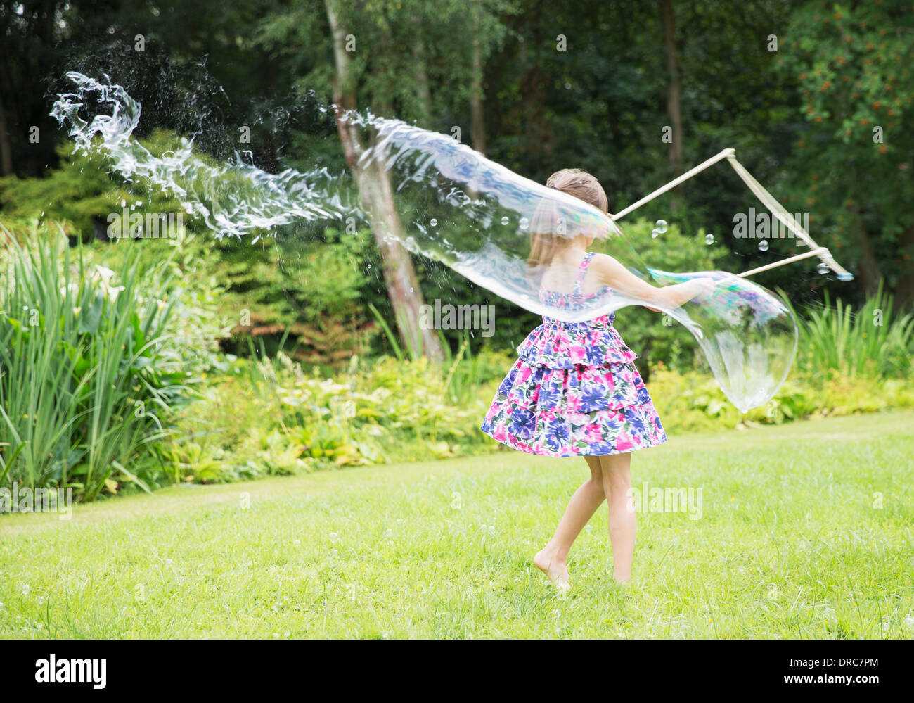 Girl making large bubbles in backyard Stock Photo