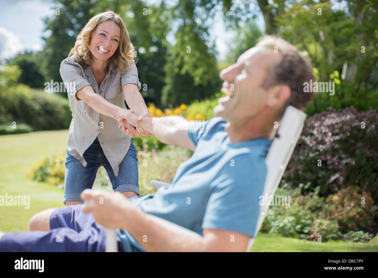 Woman pulling boyfriend out of chair in backyard - Stock Image