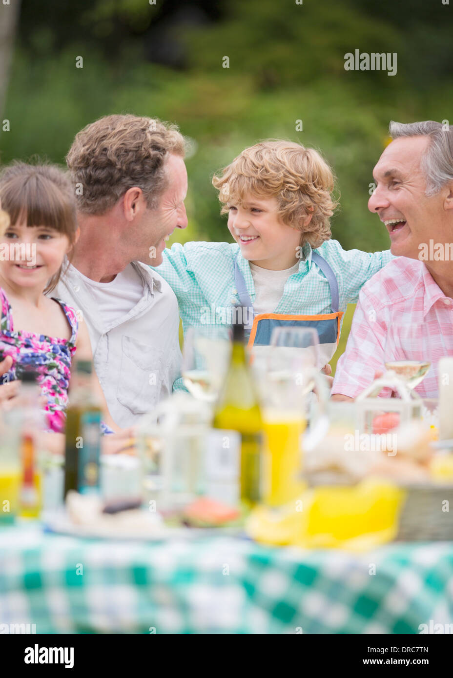 Family enjoying lunch at table outdoors - Stock Image