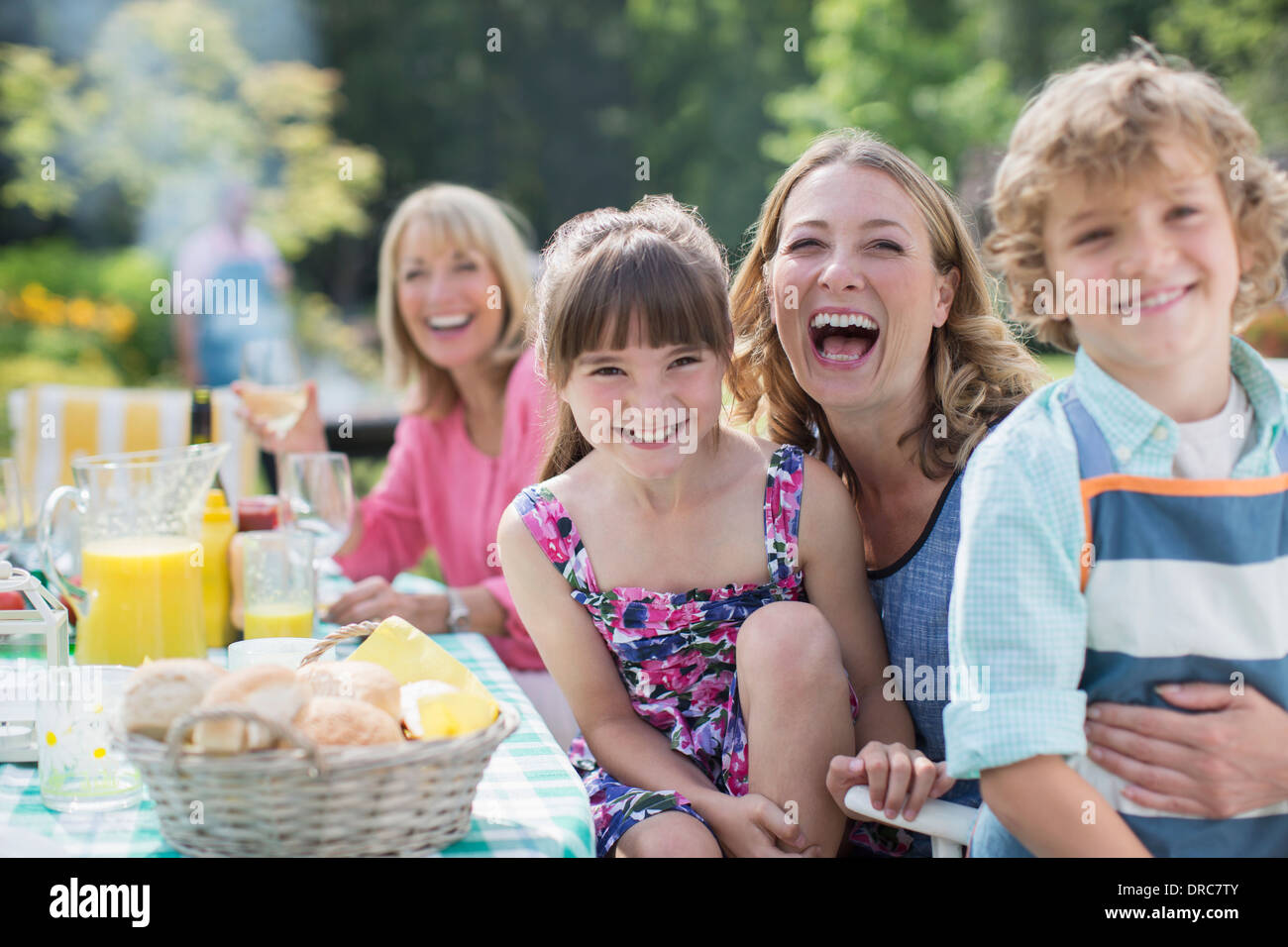 Family at table in backyard - Stock Image