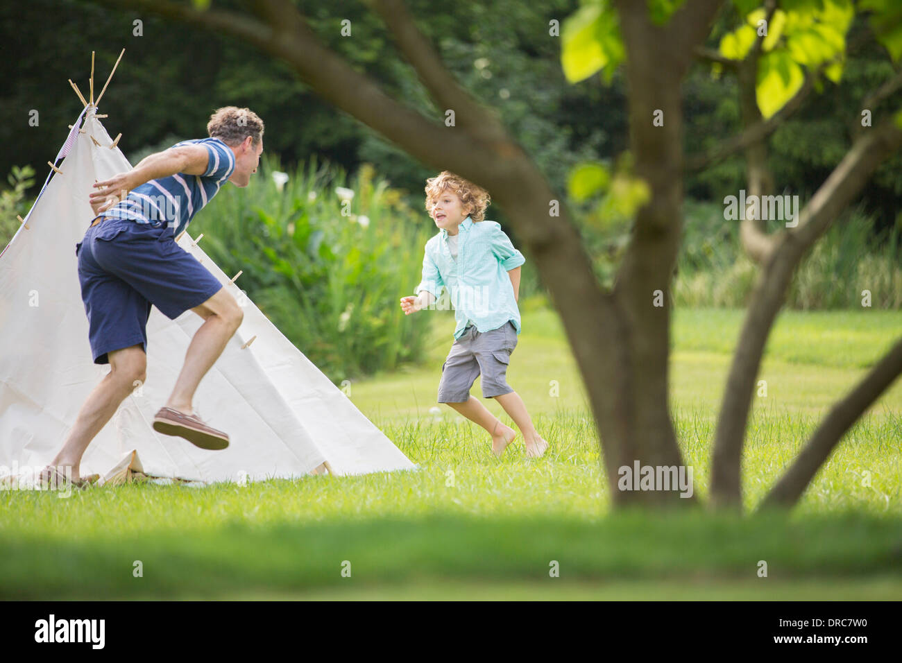 Father chasing son around teepee in backyard - Stock Image