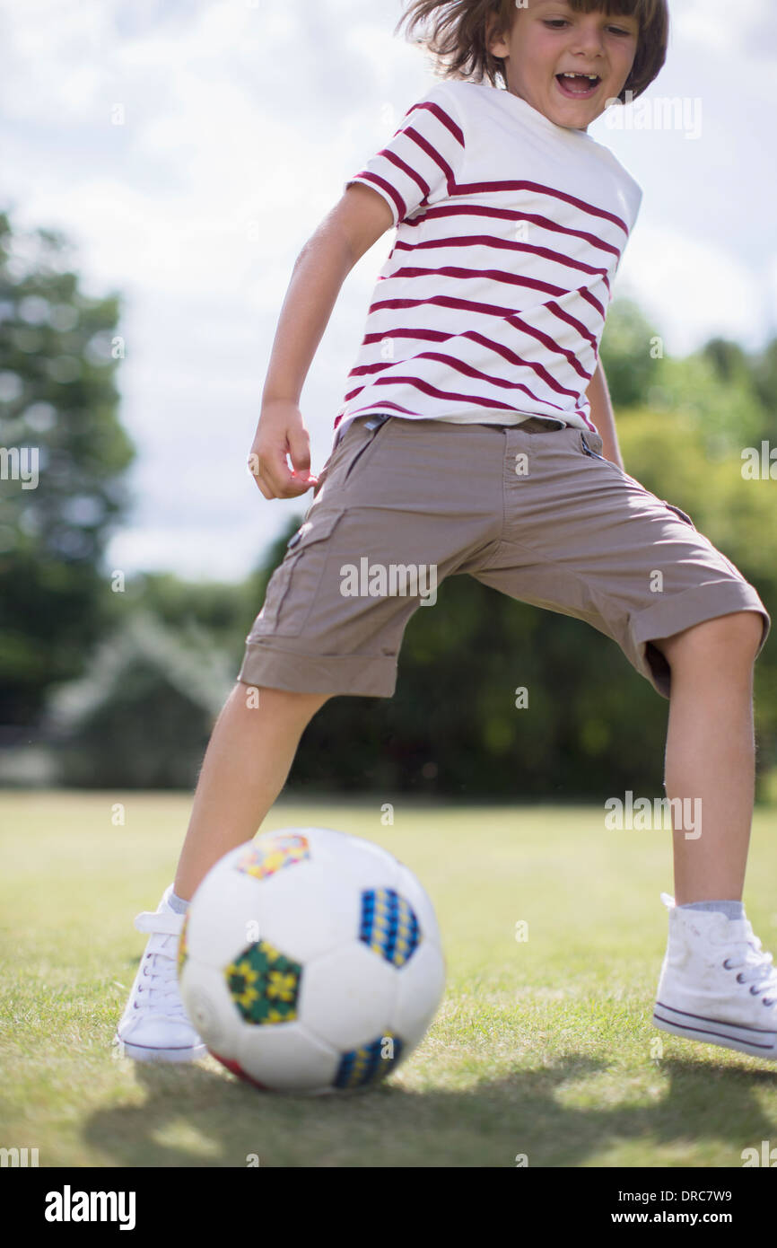Boy playing soccer outdoors Stock Photo