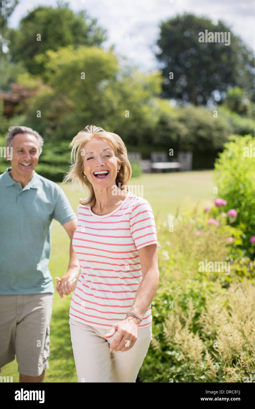 Senior couple running in backyard - Stock Image
