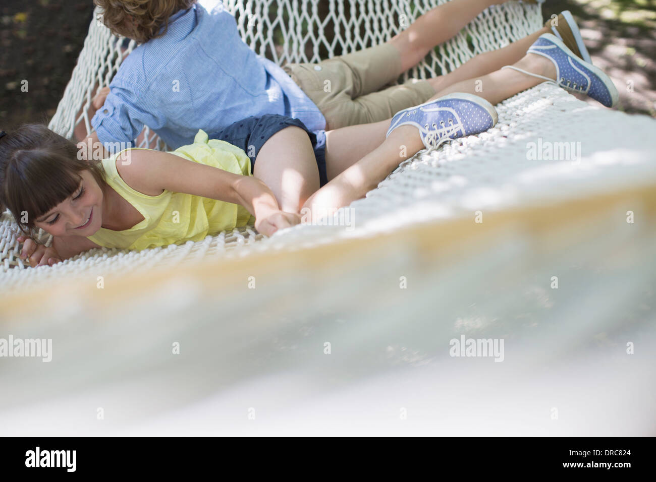 Children relaxing in hammock outdoors - Stock Image