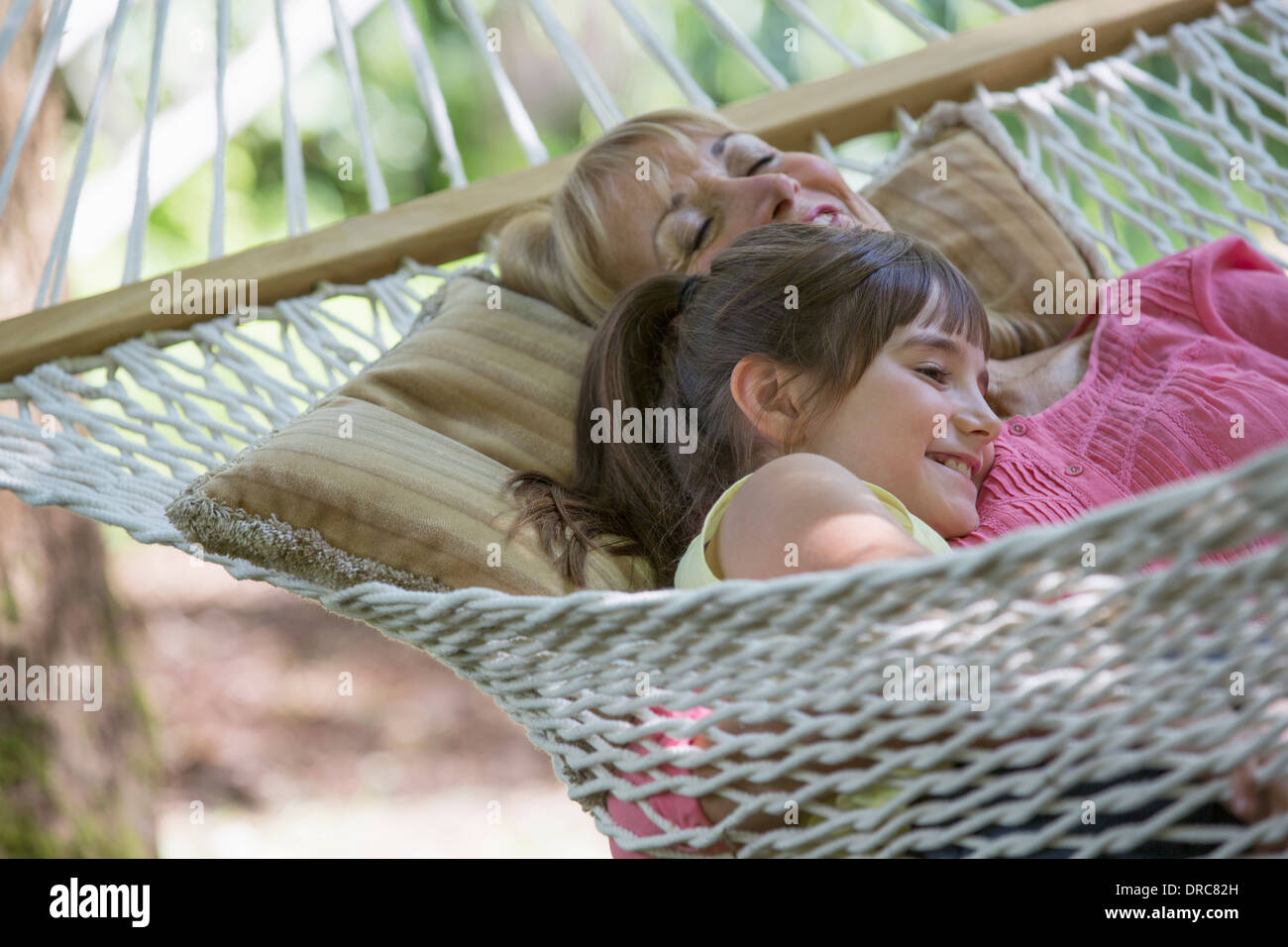Woman and granddaughter relaxing in hammock - Stock Image