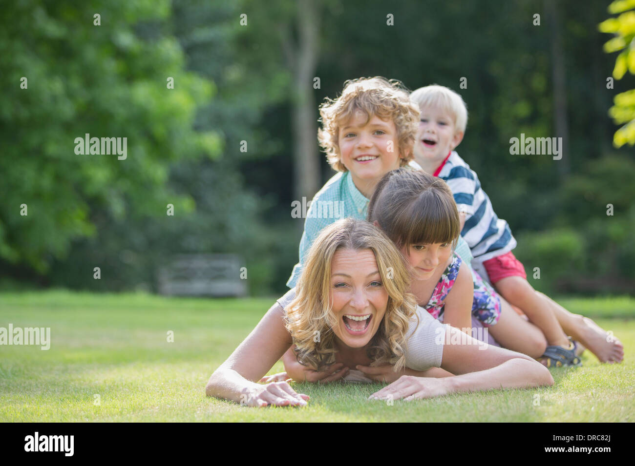Children laying on mother in grass - Stock Image