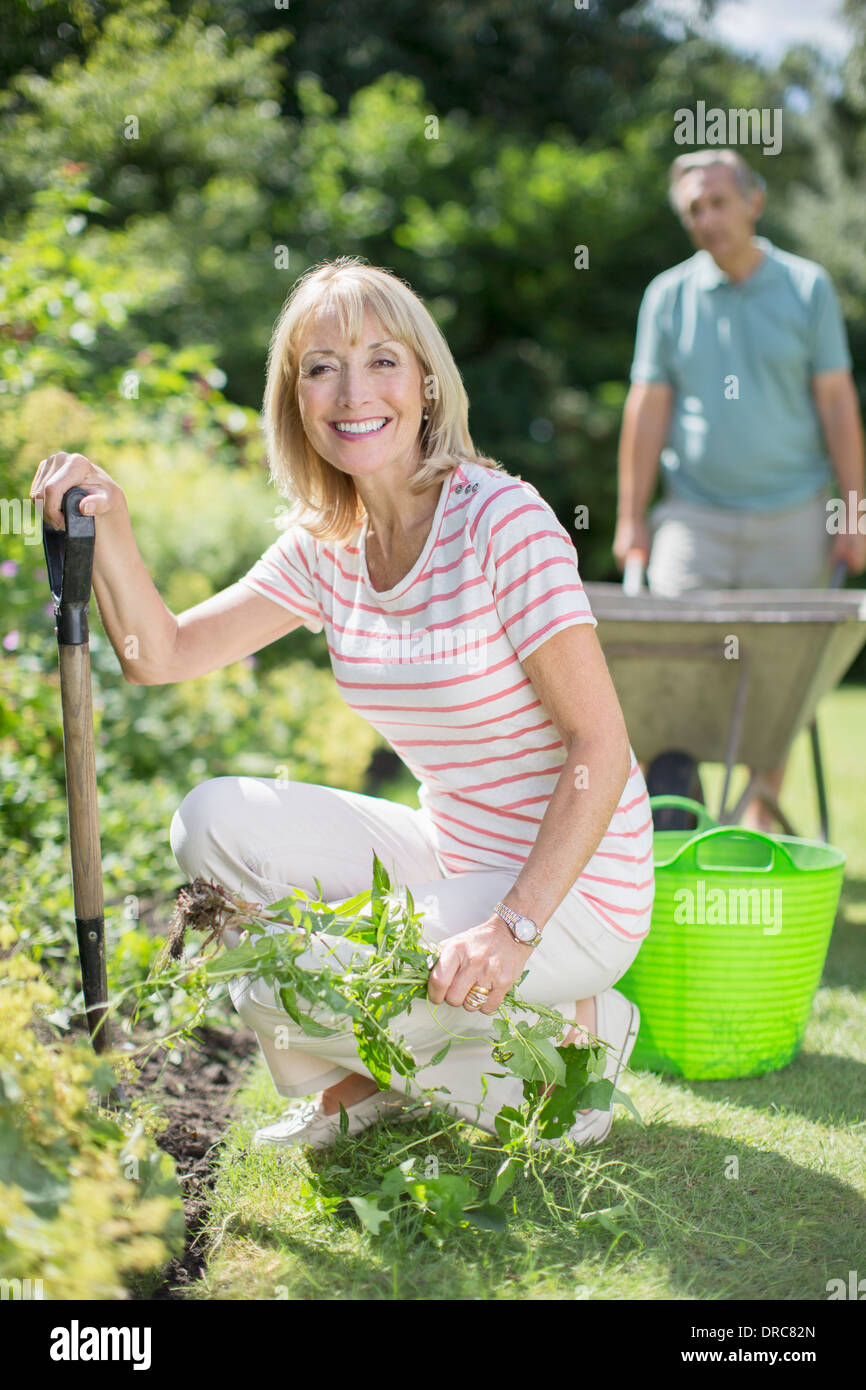 Senior couple working in garden - Stock Image