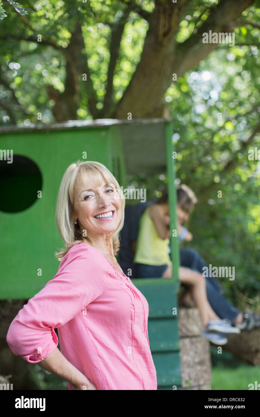 Woman smiling with treehouse in background - Stock Image