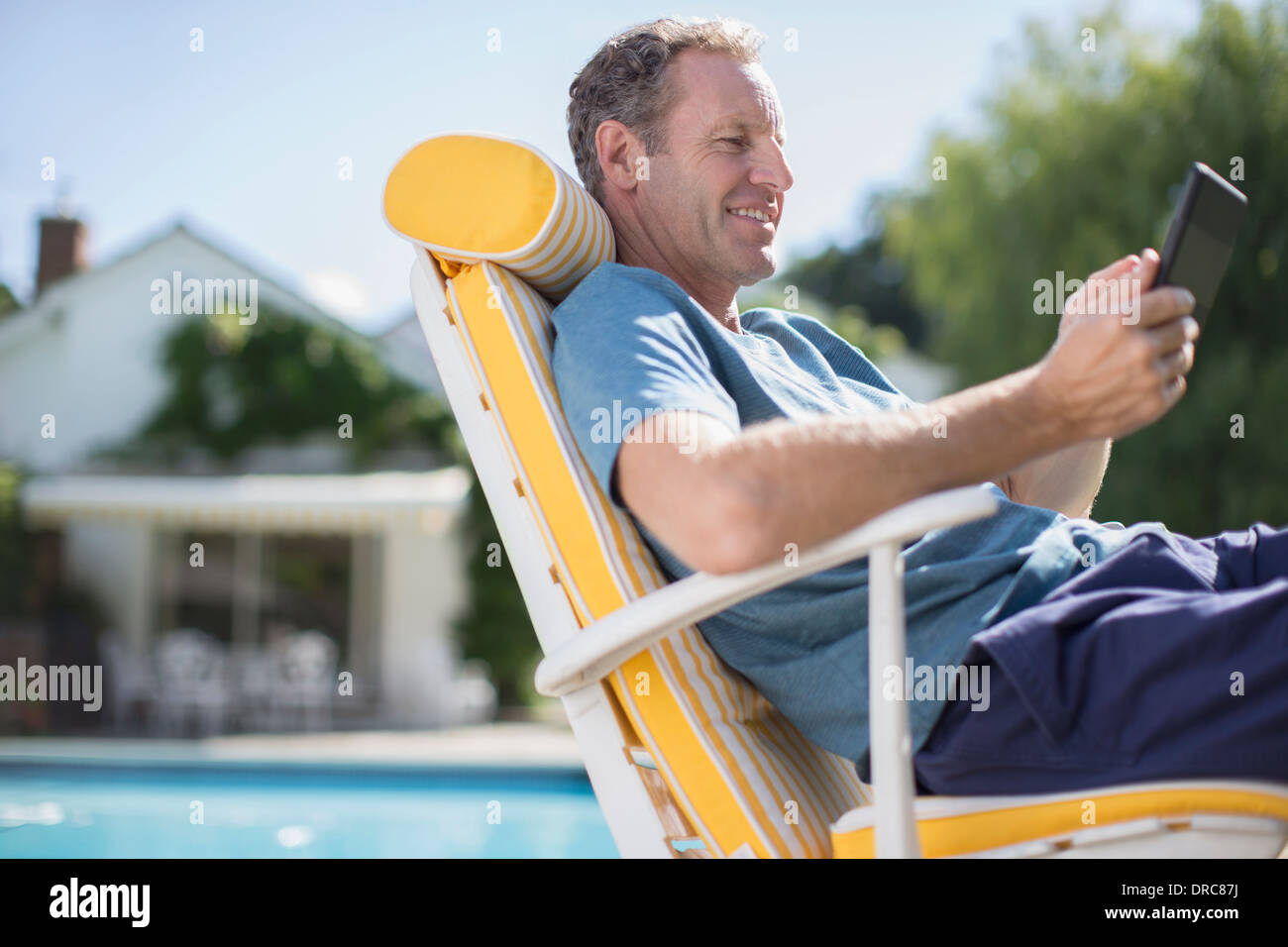 Man Reading In Lounge Chair At Poolside   Stock Image
