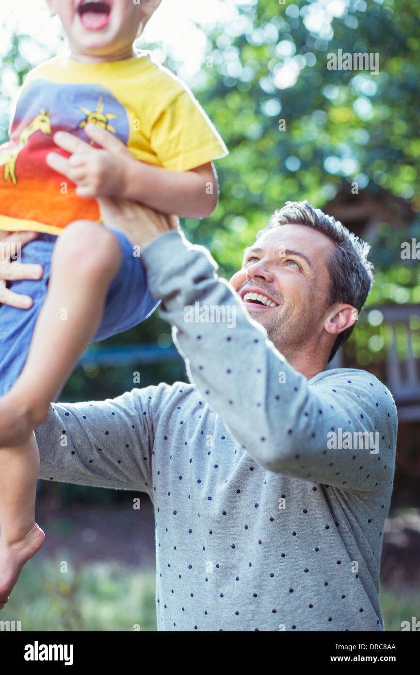 Father playing with son outdoors - Stock Image