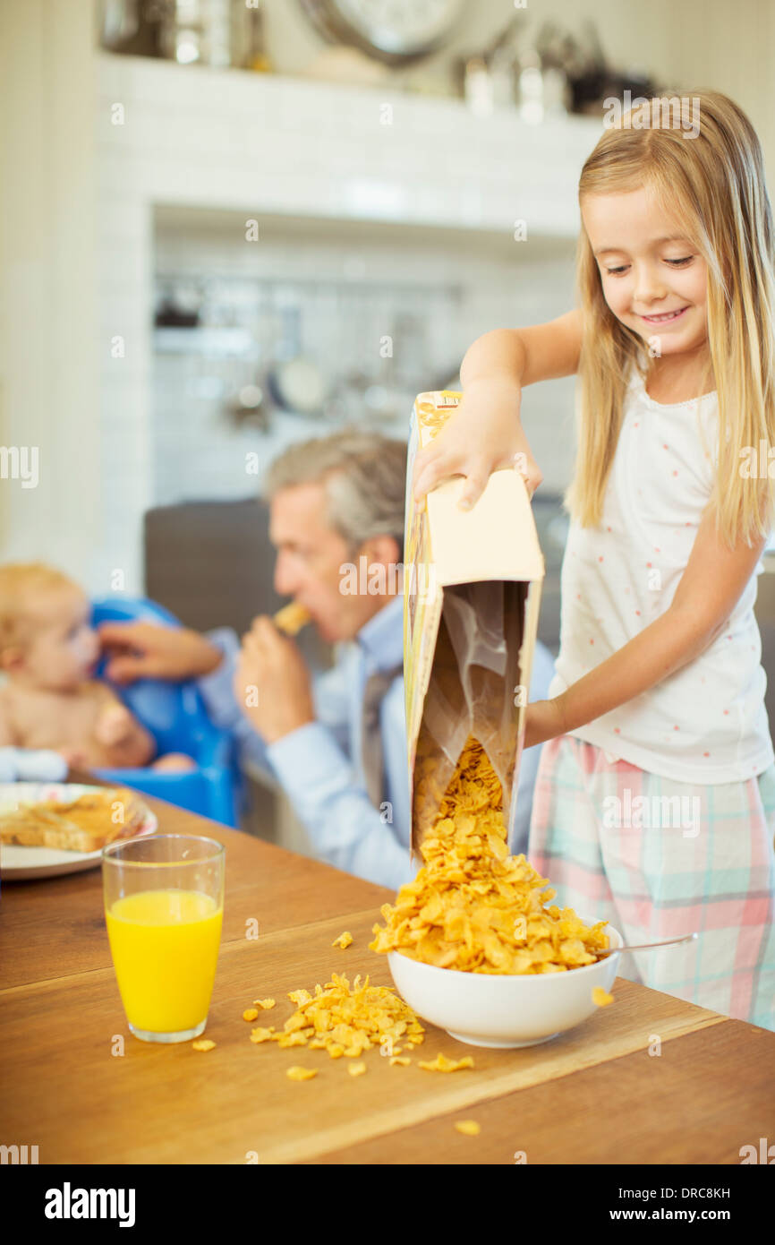 Girl pouring bowl cereal on breakfast table - Stock Image