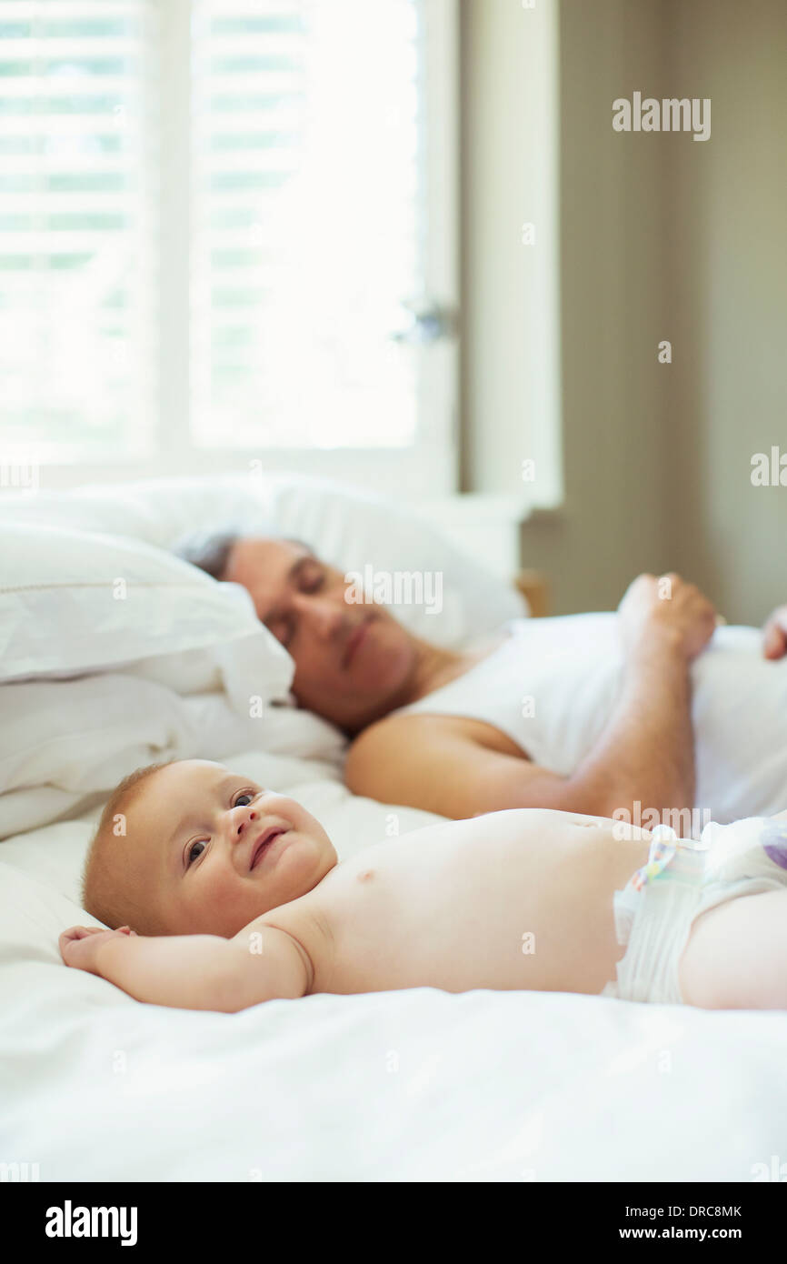 Father and baby relaxing on bed - Stock Image