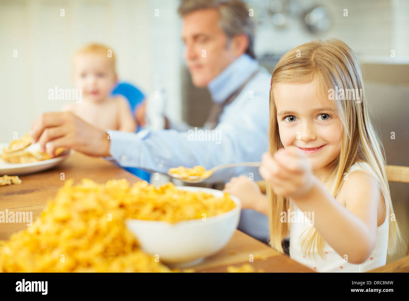 Girl eating overflowing bowl of cereal - Stock Image